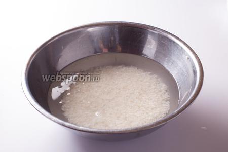Промываем рис в воде, пока она не станет прозрачной (если делать не в проточной, нужно сменить воду 5-7 раз). Заливаем рис водой и даём ему постоять минимум 15 минут, а лучше — 1 час (именно этот час указан во времени на подготовку). Сливаем эту воду и помещаем рис в скороварку. Доливаем на 1 объём сухого риса 2 объёма воды. Поэтому так важна мерная чашка для риса, а не его вес. При чём очень важно знать именно объём сухого риса, потому что при вымачивании в холодной воде он разбухает. Доводим скороварку с рисом до кипения и переводим огонь на слабый (у электрических плит — на 2), держим эту температуру 10 минут. Потом снимаем рис с огня и оставляем его в покое ещё на 10 минут.
