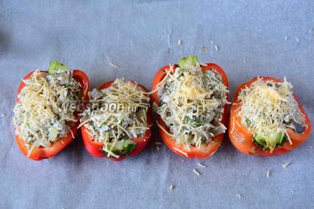 Твёрдый сыр натереть на мелкой тёрке. Посыпать перцы тёртым твёрдым сыром. Отправляем перцы в разогретую, до 180ºC духовку на 7 минут.