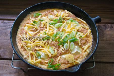 Готовый горячий омлет достать из духовки. Посыпать зелёным луком и натёртым на тёрку сыром. Готово.