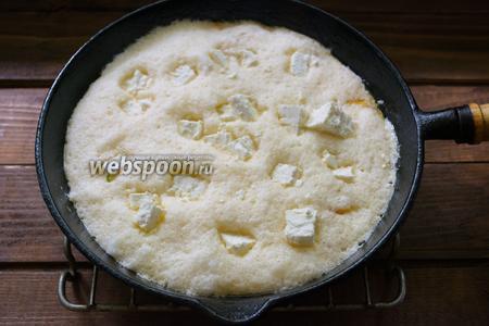 Нарезанную брынзу выложить в сырое тесто произвольно, распределив по всему омлету.