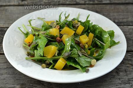 Добавить тыкву, посыпать тыквенными семечками и сверху добавить ещё немного заправки. Салат готов.