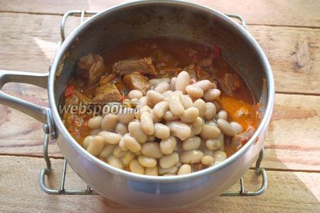 В конце приготовления добавьте фасоль вместе с жидкостью. Перемешайте. Добавьте соль и перец. Тушите 5 минут. За 1 минуту до выключения, добавьте в сотейник сметану. Перемешайте.