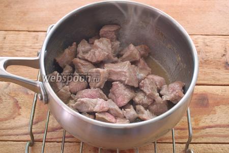 В сотейник налейте растительное масло. Разогрейте его. На масле обжарьте мясо до изменения цвета. На это уйдёт около 15 минут.