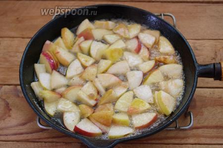 На сковороде распустите 30 г сливочного масла. Всыпьте 3 ст. л. сахара. Когда сахар начнёт кипеть, добавьте нарезанные яблоки. Не помешивая, карамелизируйте яблоки 2-3 минуты. Теперь перемешайте и снова оставьте на 2-3 минуты.