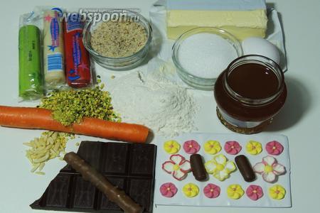Подготовим ингредиенты: муку, миндаль в крошке, яйца, масло сливочное комнатной температуры, айвовое желе, шоколад, шоколадные конфеты (шоколадные палочки с орешками), кедровые орешки для усиков, фисташки в крупную крошку, морковь, сахарные цветки, сахар и сахарную пудру, белый и красный марципан.