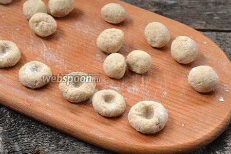 Сформировать из кусочков шарики. Прижать их на кухонной доске и сверху прижать пальцем, чтобы получилось углубление.