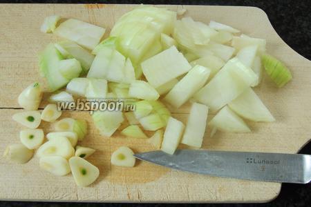 Сначала подготовим все овощи для тушения с мясом. Нарежем лук мелко и зубки чеснока на пластинки.