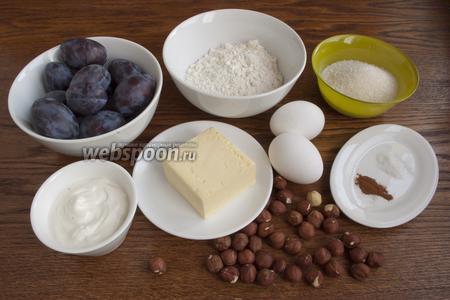 Подготовьте основные продукты для пирога: муку, сливочное масло, сахар, сливы, сырой фундук, яйца, сметану, разрыхлитель и корицу.