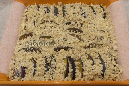 Дольки слив вдавите несильно в тесто, сверху пирог посыпьте присыпкой.