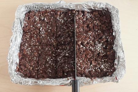 Распределите по выстланной фольгой форме, толщиной около 1 см. Понадобится прямоугольная форма размером примерно с лист А4. Посыпьте небольшим количеством кокосовой стружки и, на ещё не застывшей смеси, сделайте ножом биговку. Потом, когда смесь застынет.