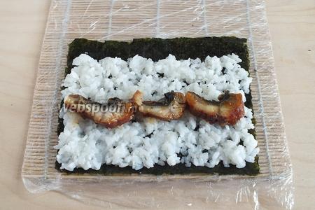 Угря нарежьте ломтиками и выложите на рис.