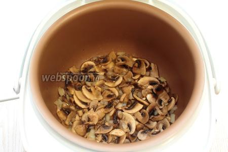 В чашу мультиварки налить масло, выложить грибы с луком. Установить режим «Жарка» на 15 минут. Обжаривать грибы и лук в течении 10 минут. Периодически открывать крышку и перемешивать.