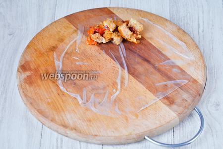 Далее выкладываем рисовую бумагу на деревянную доску (вода должна впитаться). Кладём приготовленную начинку, одной столовой ложки будет достаточно.