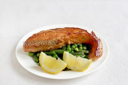 На тарелку выложить зелёные овощи, лимон (в этом случае поливать лимоном овощи, а не рыбу). Поверх овощей выложить поджаренное филе семги. Сразу подавать. Соусом полить при подаче.