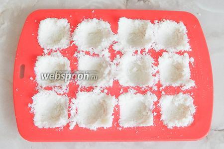Для квадратных конфеток я использую силиконовую форму. Наполняем выемки кокосовой массой так, чтобы осталось углубление для орехов. Помещаем форму в морозилку на 10 минут.