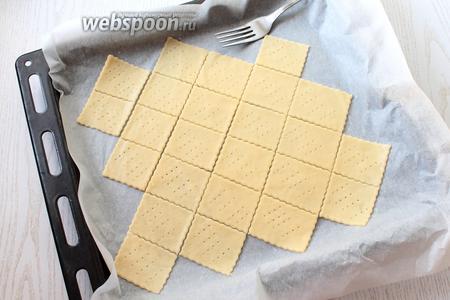 Тесто тонко раскатать на бумаге для выпечки, толщиной около 2 мм. Раскатывается оно довольно сложно, потому что содержит мало жира. Нарезать тесто на прямоугольники, обрезки теста убрать и перенести печенье вместе с бумагой на противень. Каждое печенье наколоть вилкой несколько раз. Поставить противень в разогретую духовку до 180°С.