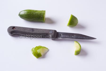 Из маленького огурца вырезаем 2 шайбочки шириной около 1-1,5 см, режем их на полукружья, и каждое из полукружий прорезаем на тонкие пластинки не до конца, чтобы потом раскрыть их в виде веера (в левом нижнем углу кадра). Таких веерочков нам потребуется 4 — по количеству роллов с нори.