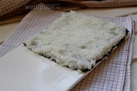 Поверх мокрыми руками распределить половину риса, разровнять.
