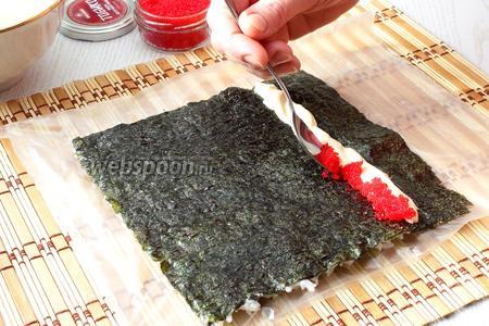 Накрываем рис другим целофановым пакетом и переворачиваем нори рисом вниз, к себе ближе той частью нори, под которой нет риса, верхний пакет убираем. Теперь можно выкладывать начинку. Сначала выкладываем полосочку сыра, затем икру тобико летучей рыбы.