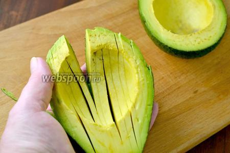 Нарезаем мякоть авокадо пластинками толщиной 0,4-0,5 см, стараясь не прорезать кожуру. Затем немного выворачиваем половинку и снимаем кожуру.
