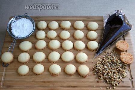 Приготовить всё для сборки печенья. В кондитерский мешочек выложить шоколадную начинку. Орехи мелко порубить ножом. Ситечко наполнить сахарной пудрой.