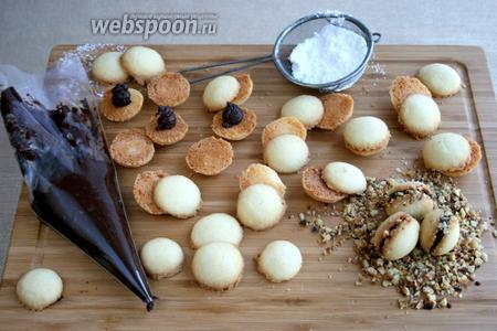 Подобрать половинки печенья по размеру. Нанести на половинку начинку, накрыть другой половинкой. «Прокатать» колёсиком в измельчённых орехах. Так приготовить всё печенье.