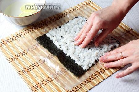 Берем 115-120 г риса, чтобы рис к рукам не прилипал руки смачиваем в воде с лимоном. Рис равномерно раскладываем на водоросли, сверху оставляя 2-3 см.