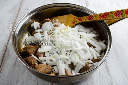 Добавить к мясу подготовленные лук и чеснок. Перемешать. Жарить в течение 5-7 минут, помешивая.