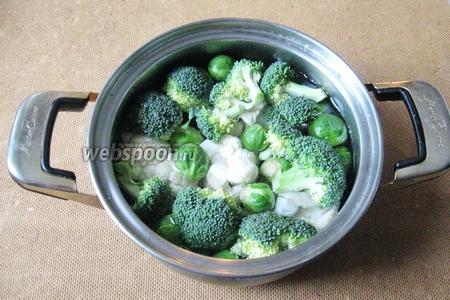 Цветную капусту и брокколи разбираем на соцветия, кладём в кастрюлю. Добавляем брюссельскую капусту. Варим капусту в подсоленной воде до готовности: брокколи 5-7 минут, цветную и брюссельскую 10-15 минут.