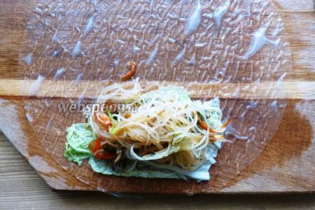 Кладём рисовый блинчик на удобную вам поверхность (у меня деревянная доска). Теперь собираем спринг-ролл. Сначала на блинчик кладём кусочек пекинской капусты, на неё 1-2 столовые ложки начинки.