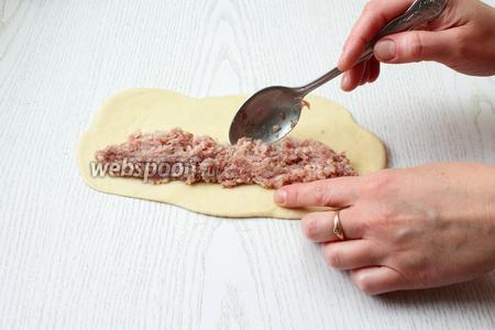 Кусочек теста раскатайте в длину, толщиной около 5 мм. Вдоль одного края выложите мясную начинку.