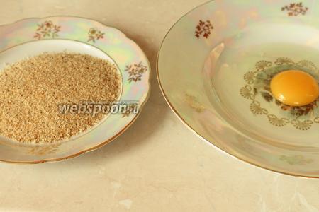 Для панировки на плоскую тарелку высыпать сухари, в глубокой тарелке слегка взболтать яйцо.