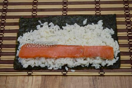 Выкладываем слой риса на нори, на рис кладём кусочки лосося.