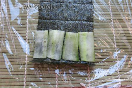 Ещё одна часть буквы — «салатовые» чернила — на нори кладём пластинки огурца, отступаем от края.