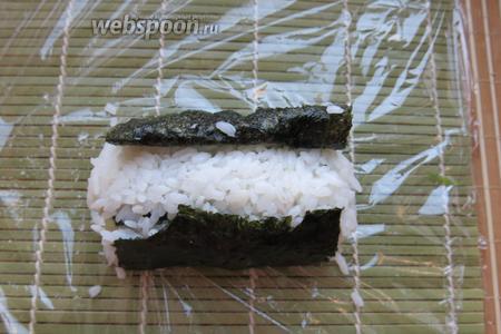Сверху и сбоку выкладываем рис, поднимаем листы нори, заворачиваем.