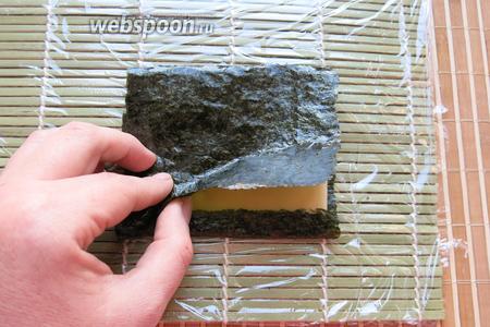 Закрываем сыр нори, чуть смачиваем лист водой. Аналогичную операцию будем повторять и с другими продуктами.