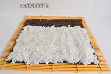 Рис промыть до прозрачности  и отварить до готовности. Остудить и добавить в него 1 столовую ложку рисового уксуса, перемешать. Соль и сахар не добавляю, большинство рисовых уксусов для приготовления суши уже содержат в своем составе сахар и соль. Руки смочить уксусом и выложить рис тонким слоем на лист нори, 1/5 части листа оставить непокрытой рисом. Ладонями прижать рис к нори, то есть уплотнить слой риса. Так легче будет скручивать ролл. Лист нори нужно класть шершавой стороной вверх.
