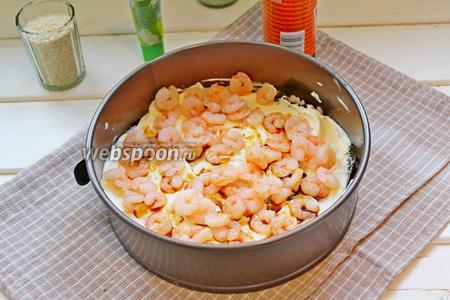 Сверху выложить половину мелких креветок и сбрызгнуть их соевым соусом.