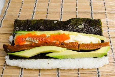Разложить начинку: слоями — авокадо, угорь, сливочный сыр, огурец. На сливочный сыр разложить икру тобико.