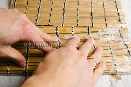 С помощью макисы плотно прижать слой риса.