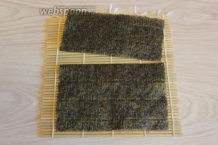 Отрежьте половину или 2/3 листа нори в зависимости от размером заготовки огурца или в зависимости от желаемых размеров цветка. Уложите нори блестящей стороной на макису/циновку.