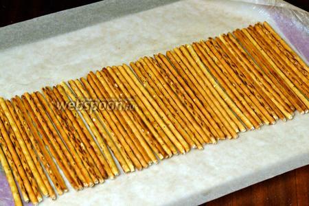 Смазываем кусочком сливочного масла середину бумаги для выпечки и раскладываем в рядок соломку, убирая попоманные.