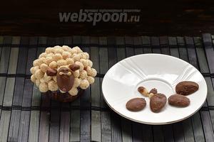 Для отделения шоколада от кофейных ложек, опустить их нижней стороной в горячую воду. Шоколад легко отделится. Половинки арахиса можно обмакнуть в шоколад для «ушек». Прикрепить мордочку и ушки овце. Прикрепить глаза и нос.