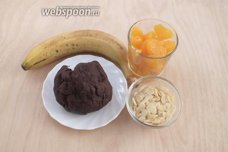 Теперь можно приступить к приготовлению ролла. Возьмите получившуюся шоколадную массу (она уйдёт вся), банан, консервированный мандарин и миндальные лепестки. Вместо мандарина можно взять любые фрукты и ягоды по вкусу. С мандаринов полностью слейте сок и обсушите на салфетке.
