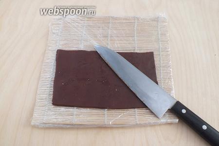 Шоколадную массу нужно раскатать. Старайтесь не разминать её руками, она быстро тает, расплющивайте её пластиковой скалкой прямо на столе. Затем раскатайте в пласт толщиной примерно 0,3 см и вырежьте 3 прямоугольника размером 12х18 см. Если касаться массы только скалкой и ножом она выглядит как матовый пластилин. Кладём наш шоколадный прямоугольник на циновку-макису, обернутую плёнкой.
