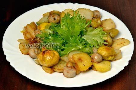 Окружаем зелёный салат обжаренным картофелем, каштанами и колбасками. Подаём сразу же, пока основная масса салата не остыла. Соус можно добавлять по желанию в порционную тарелку.