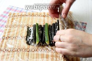 Поверните коврик цветком к себе и аккуратно сверните ролл, соединяя края нори.