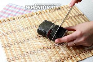 Острым ножом, смоченным водой, разрежьте ролл пополам, каждую половинку еще раз пополам.