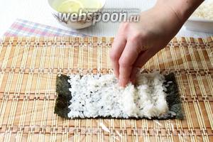 На половину другого листа нори выложите рис, распределите рис по водорослям. Затем сделайте четыре рисовых холмика.