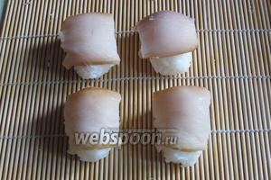 Сверху на рис выложить кусочки рыбы, слегка растянув её по длине риса.